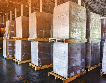 Worker driving forklift loading shipment carton boxes goods on wooden pallet at loading dock from container truck to warehouse cargo storage in freight logistics, transportation industrial, delivery 스톡 콘텐츠 - 155124465