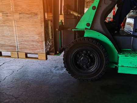 Worker driving forklift loading shipment carton boxes goods on wooden pallet at loading dock from container truck to warehouse cargo storage in freight logistics, transportation industrial, delivery 스톡 콘텐츠 - 155124553
