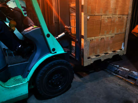 Worker driving forklift loading shipment carton boxes goods on wooden pallet at loading dock from container truck to warehouse cargo storage in freight logistics, transportation industrial, delivery 스톡 콘텐츠 - 155124634