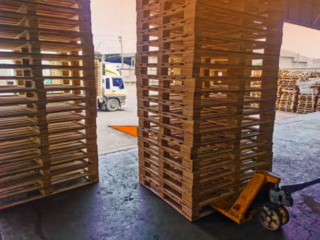 Worker driving forklift to loading and unloading wooden pallets from truck to warehouse cargo storage, shipment in logistics and transportation industrial, wood pallets stack 写真素材