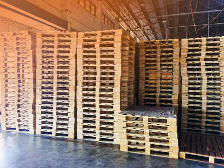 Worker driving forklift to loading wooden pallets from truck to warehouse cargo storage, shipment in logistics and transportation industrial, wood pallets stack