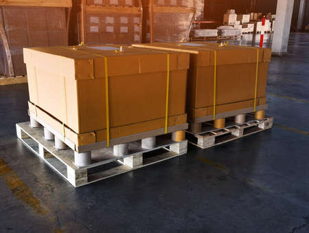 Shipment cartons box on pallets and wooden case on hand lift in interior warehouse cargo for export