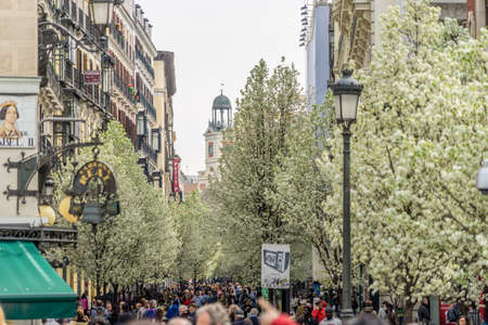Madrid, Spain. March 21, 2017. People walking along blooming cherry trees from Plaza de Isabel II along Arenal street (Calle del Arenal) to Puerta del Sol square and clock tower Editorial