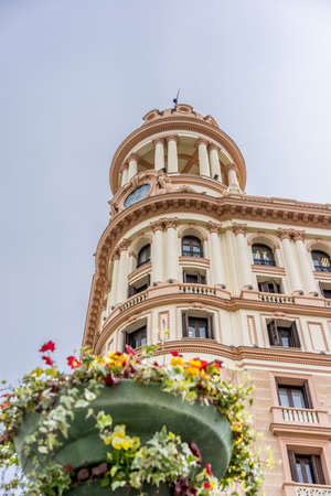 Madrid, Spain. March 21, 2017. Street level view of Vitalicio Building tower and foreground blurry flower decoration of Callao Square. Located in the junction of Gran Via and Leganitos street.