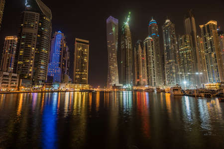 Dubai Skyline at night with colorful reflections on the water