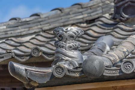 Kamakura, Japan. August 15, 2015. Roof ornament (Botan no kazari kawara) from Tatsumi Jinja Shrine (Tatsumi Kojin) of deity Okutsuhiko no Kami or Kojin-sama, protector of kitchens and cooking fires