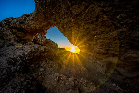 Sunset and mountain landscape view from eroded stone arch know as Ventana del nublo or La Agujereada. One of the higest places in Gran Canaria Island. Stock Photo