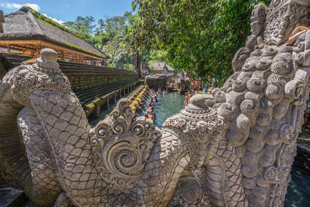 Bali, Indonesia - Sept. 9, 2017. Guardian Sculpture and Worshippers during purification ceremony at Pura Tirta Empul temple Holy Spring Waters