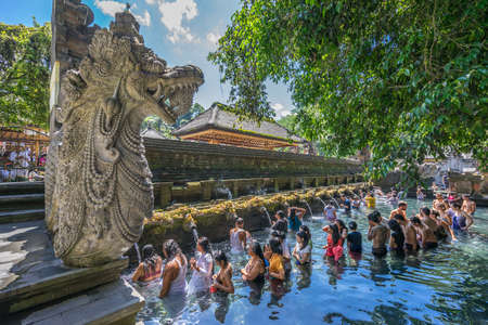 Bali, Indonesia - Sept. 9, 2017. Worshippers at cleansing ceremony at Pura Tirta Empul temple Famous for its Holy Spring Waters
