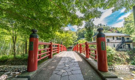 Izu, Shizuoka, Japan - August 10, 2018 :  Kaedebashi Bridge over the Kitamata river in the Shuzenji hot spring area of Izu City. Narrrow path bamboo grove in the back.