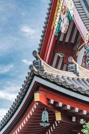 Tokyo, Taito Ward - August 18, 2018 : Onigawara ogre goblin tile roof ridge detail, Crooked cross and Kazarikanagu Metal ornaments roof ridge deatil at Senso-ji temple 写真素材 - 130701642