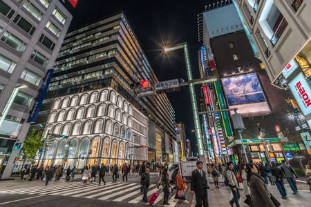 Ginza, Tokyo - December 2017 : Illuminated billboards in crowded Chuo dori street at Ginza luxurious shopping District by night.