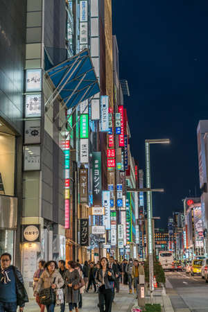 Ginza, Tokyo - December 2017 : Billboards, neon signs and People enjoying nightlife in crowded Chuo dori street at Ginza luxurious shopping District by night. 에디토리얼