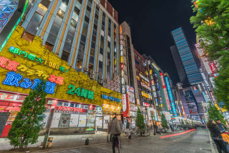 Kabukicho, Shinjuku, Tokyo, Japan - November 20, 2017 : Colorful busy Street and Billboards. Motion blurred People passing along Shops around Yakusuni Dori at night. Редакционное