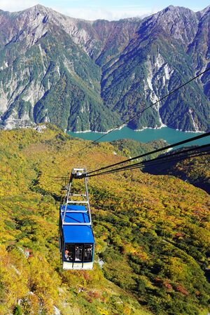 Rope Way and Cable Car Is Lifting People And A Valley And Lake On The Background. Tourist Going Up To The Mountain.