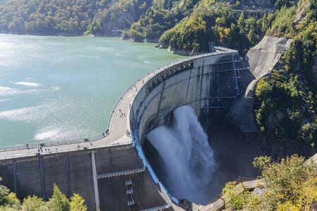 Wasserturbinen produzieren Strom im Kraftwerk. Panoramaansicht des Wasserkraftwerks und der Menschen auf dem Kurobe Lake Dam, Toyama. Flussdamm und Tateyama-Berge. Standard-Bild