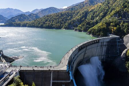 Panorama View Of Kurobe Lake Dam In Toyama. River Dam And Tateyama Mountains On Sunny Day. Reklamní fotografie