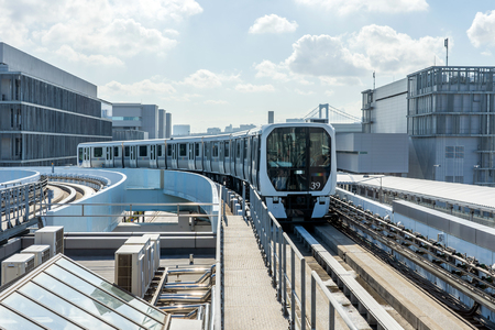 The Monorail Train Is Approaching Station On A Sunny Day. The White Metro Train Is Arriving To The Platform On Open Air Track In Tokyo, Japan.