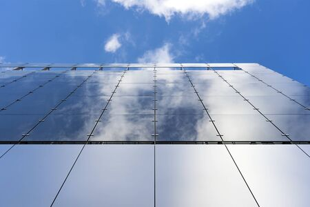 Glass And Aluminum And Blue Sky And Modern Architecture. Clouds Are Reflecting In The Glazing Facade And Silver Colored Aluminium Panels. Stockfoto