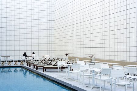 Two Women Are Sitting And Talking Next To Open Air Swimming Pool. Фото со стока