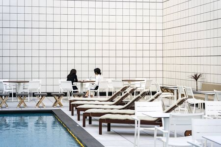 Two Ladies Are Sitting And Talking Next To Open Air Swimming Pool. Фото со стока