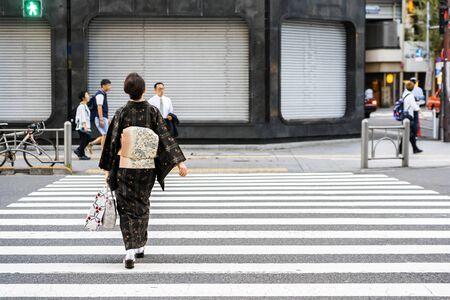 TOKYO, JAPAN - OCTOBER 6, 2018. Japanese Woman is Crossing Road Wearing Japanese Traditional Dress. Lady is in Kimono on Street in Tokyo.