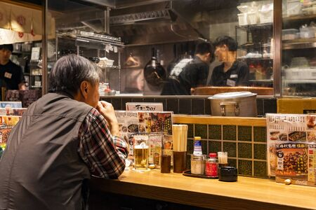 TOKYO, JAPAN - OCTOBER 6, 2018. Man is Waiting for his Order and Drinking Beer in the Japanese Restaurant. Men are Cooking a Meal. Stockfoto