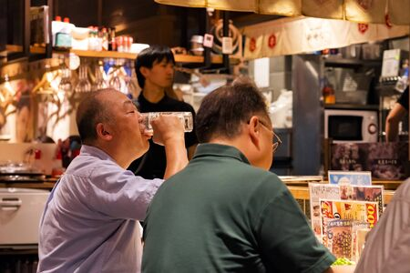 TOKYO, JAPAN - OCTOBER 6, 2018. Men are having the Dinner and Drinking Beer in the Japanese Restaurant. Old Friends are having Meal.