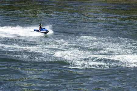 Man is Riding The Ski Jet. Water Splashes from Fast Speed Boat.