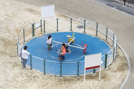 Children are Playing on The Playground While Their Mom is Watching. Kids are Riding Roundabout. Two Young Girls are Having Fun. Stockfoto