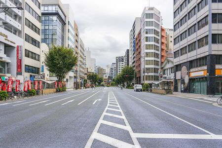 TOKYO, JAPAN - OCTOBER 8, 2018. Empty Wide Road in Tokyo. People are Crossing Road.