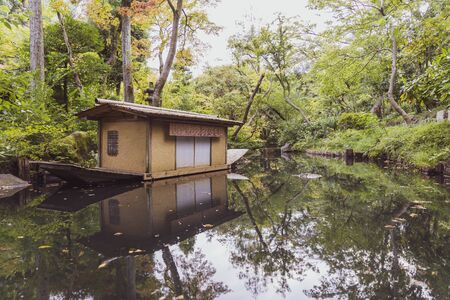 Reflection of the Oriental Houseboat in the Pond. The Japanese House Boat, Lake, River and Green Forest.