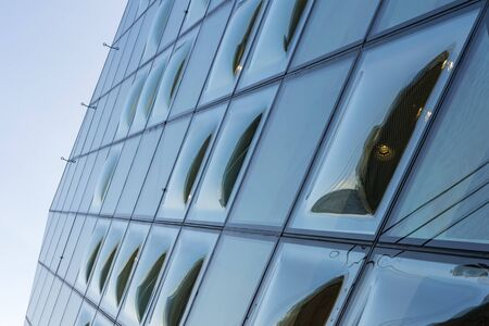 Close-Up View of Double Curve Convex Glass Windows. Reflected Clear Glazing Facade System. The bubbles of Glass Panels.