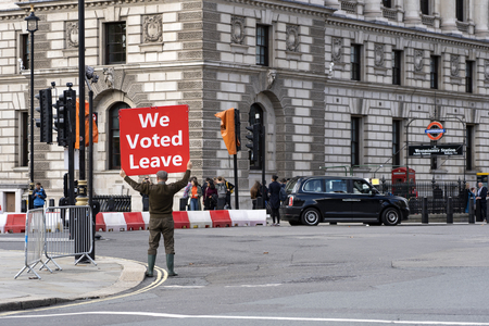 LONDON, UNITED KINGDOM - OCTOBER 1, 2019. Old Man is Holding the Red Banner on the Parliament Square Supporting Brexit - We Voted Leave. Redactioneel