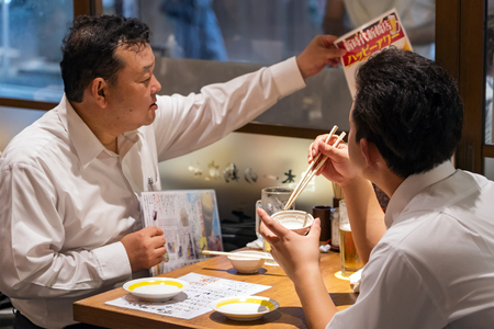 TOKYO, JAPAN - OCTOBER 6, 2018. Japanese Salary Men are having the Dinner and Drinking Beer in the Japanese Restaurant. Old Friends are having Meal. Éditoriale