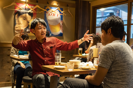 TOKYO, JAPAN - OCTOBER 6, 2018. Guys are having the Dinner and Drinking Beer in the Japanese Restaurant. Young Friends are having Meal.