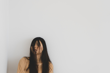 TOKYO, JAPAN - OCTOBER 8, 2018. Portrait Photography of the Pretty Sleeping Asian Girl. Half Of Face Covered By Womans Hair. White Background.