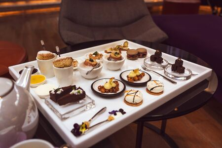 Luxury Afternoon Tea Set on the Table for Two People. Delicious Desserts Served on the Table.
