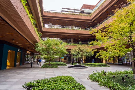 SHANGHAI, CHINA - NOVEMBER 10, 2018. Ruihong Tiandi Shopping Mall. External Courtyard of a Retail Complex with Lush Greenery. Garden with Footbridge and Terraces. Green Sustainable Architecture.