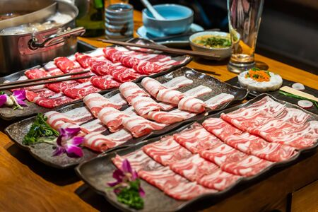 Selection of meat platters to be cooked in hotpot restaurant, including beef, lamb and pork. All thinly sliced for quick cooking. Sauces and pot in background 스톡 콘텐츠
