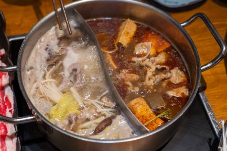 Customized combo pot with boiling hot soups, one spicy flavor and one mushroom flavor. 스톡 콘텐츠