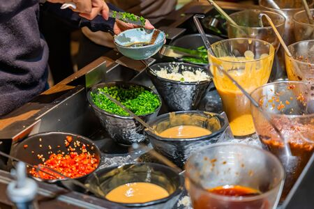 Customize hotpot colorful sauce at the station in restaurant, a wide variety of choices available. Hand is mixing sauces.