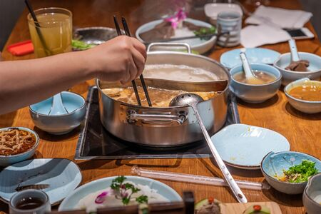 A diner picking out food from boiling soup in hotpot restaurant by long chopsticks