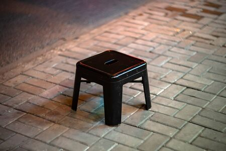 The black metal stool is near street restaurant on the ground. The small chair stands on the sidewalk at street night market.