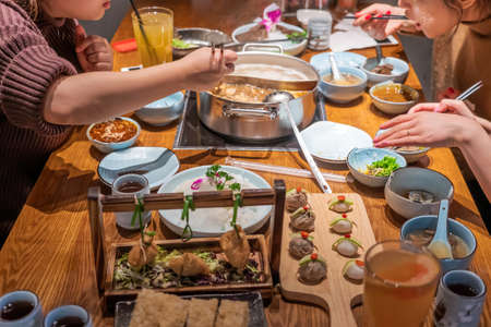 Table full of dishes and ingredients to be cooked in hotpot restaurant, with three diners