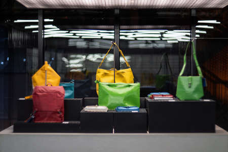 SHANGHAI, CHINA - NOVEMBER 28, 2018. Retro film photo with blurred background. Fashionable colourful bags made from recycled materials are displayed in the hipster shop. Several backpacks are on the stand in a store.