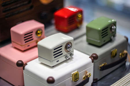 SHANGHAI, CHINA - NOVEMBER 28, 2018. Retro film photo with blurred background. Vintage style small radio are in a gift shop. Modern speakers stylized to old and colorful design devices. 에디토리얼