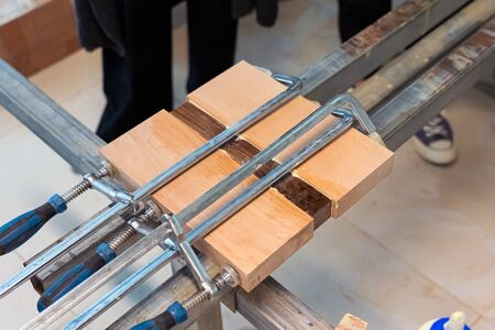 Three Wooden Bars are Glued to Each Other at Woodwork. Wood Pieces Fixed by Jaws Vise Tongs. 스톡 콘텐츠