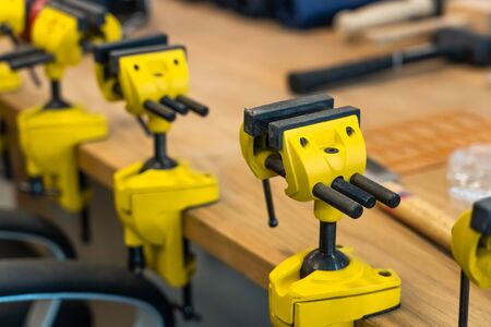 Many Yellow Vises are Set on the Work Bench at the School. New Grips or Jaw Vices Fixed at Woodwork Workshop. 스톡 콘텐츠