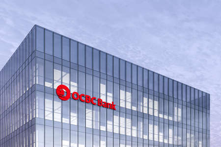 Singapore. February 27, 2021. Editorial Use Only, 3D CGI. OCBC Bank Signage Logo on Top of Glass Building. Oversea-Chinese Banking Corporation Company in High-rise Office Headquarter.